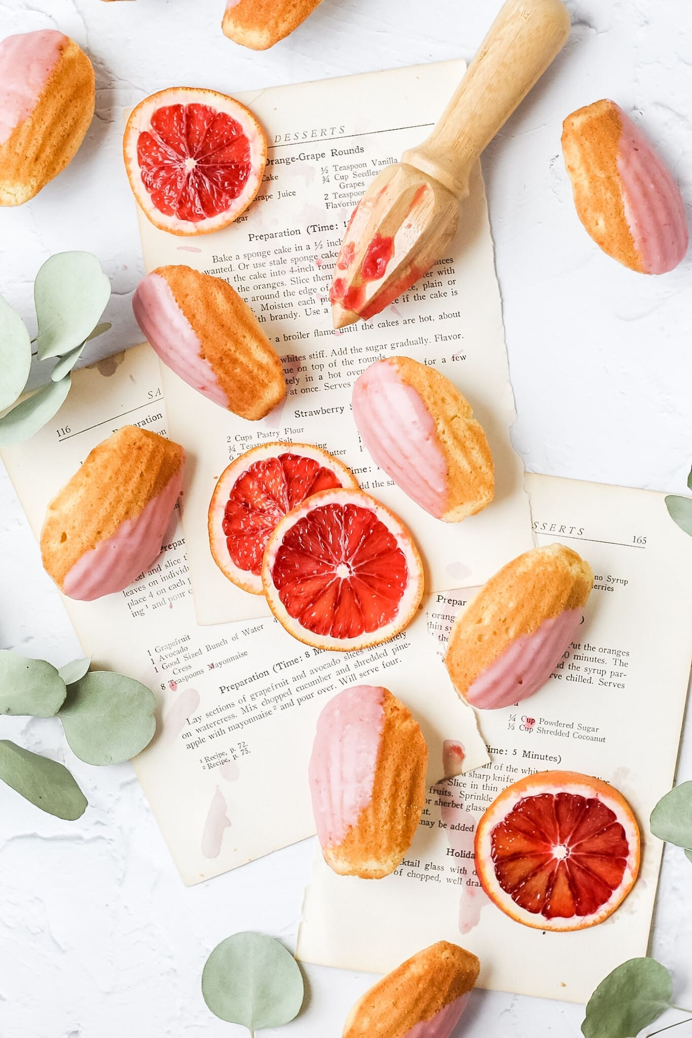 madeleines dipped in blood orange glaze with slices of blood oranges and citrus reamer